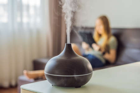 Aromatherapy Concept. Wooden Electric Ultrasonic Essential Oil Aroma Diffuser and Humidifier. Ultrasonic aroma diffuser for home. Woman resting at home Foto de archivo