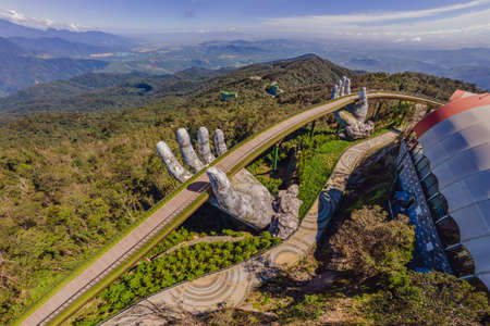 Top aerial view of the famous Golden Bridge is lifted by two giant hands in the tourist resort on Ba Na Hill in Da Nang, Vietnam Standard-Bild