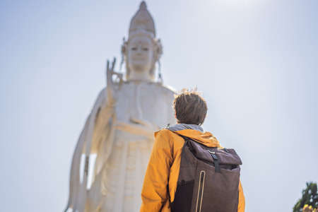 Male tourist on the background of Majestic view of the Lady Buddha statue the Bodhisattva of Mercy, Vietnam. White Ladybuddha statue on blue sky background