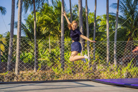 Young woman jumping on an outdoor trampoline, against the backdrop of palm trees