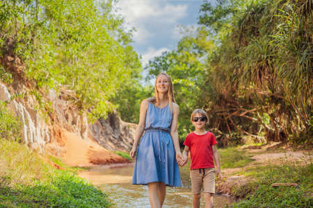 Mom and son tourists on the Fairy stream among the red dunes, Muine, Vietnam.