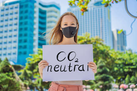woman in medical mask holds a poster Lettering text CO2 Neutral Imagens