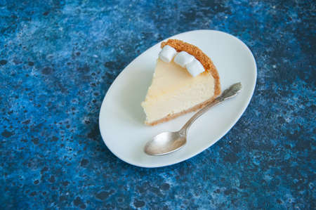 Slice of New York Cheesecake  style with marshmallows on white plate on blue background Stock Photo