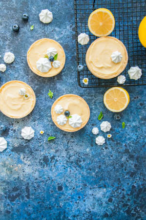 Individual lemon curd tarts with blueberry jam meringue basil leaves on a blue rusty background. Flat lay and copy space.
