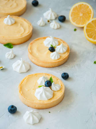 Individual lemon curd tarts with blueberry jam meringue and basil leaves on a white stone background. Flat lay and copy space.
