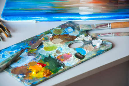 palette knife: Art brushes and palette with oil paints on a table. Painting concept.