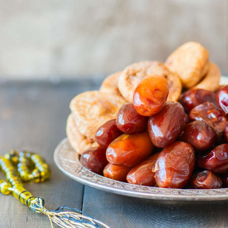 Close up of dried date fruits or kurma and figs served on a old vintage plate with ornaments and beads on a wooden background, ramadan food concept.