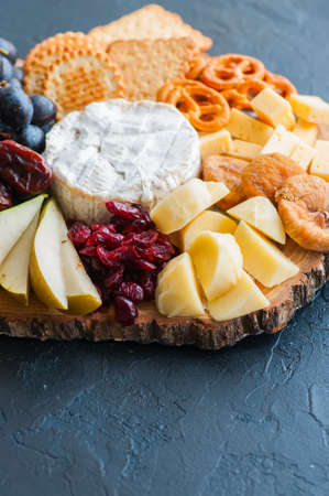 Cheese plate grape salted craker cookies dry dates cranberry, fig, pear pretzels on a wooden board on a black slate background.