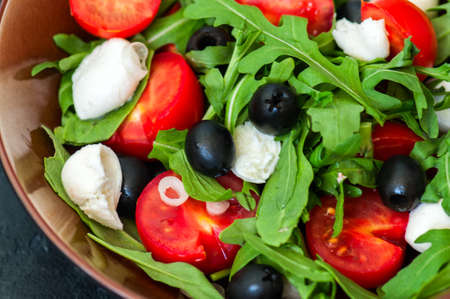 Close up of fresh salad with rucola, tomatoes cherry, olives, spring onion, mozzarella and spices in a bowl on a black slate background with copy space. Healthy food, Diet, Detox, Clean Eating or Vegetarian concept