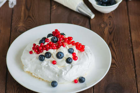 Close up of homemade meringue cake Pavlova with whipped cream with mascarpone, fresh blueberries and red currants in a white plate on a wooden background. Stock Photo