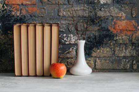 Libros antiguos, manzana y brunches en florero. Humor de otoño, conceptos de lectura Foto de archivo - 84875266