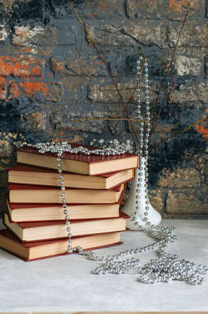 Stack of old books, branches in vase with garland, brick background