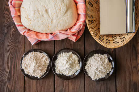 Homemade dough, sourdough in a jar, mix of flours, bread and basket for proof and spatula on a wooden background. Baking concept. Reklamní fotografie