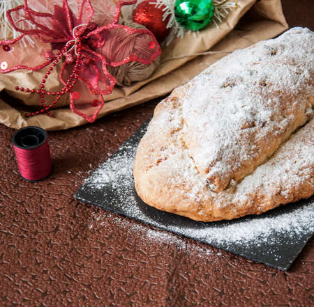 German stollen - Traditional European Festive Baking. Festive Christmas cake with dry fruits and almonds served on stone board on the table with Xmas decorations. Selective focus. Copy Space.