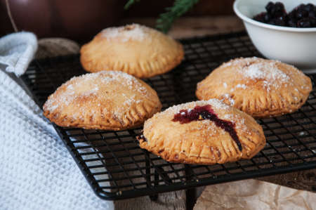Blueberry hand pies sprinkled with sugar on wooden table.