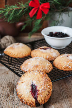 Blueberry hand pies sprinkled with sugar on wooden table with christmas tree branch Stock Photo