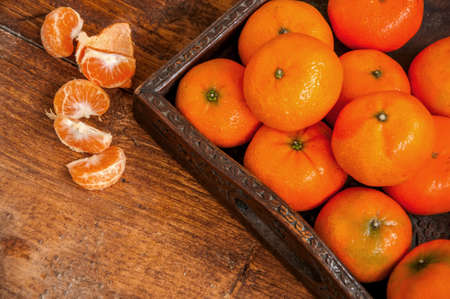 A group of fresh tangerines (mandarins) in wooden tray on old wooden background. Close up. Copy space. Stock Photo