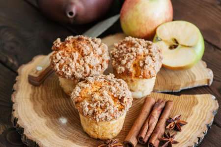 Apple cinnamon crumble muffins, spices and half of apples on a wooden board. Wooden background. Close up and copy space.