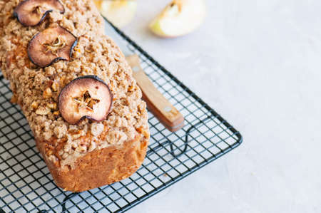 Holland apple crumble bread served on a wire rack on a white stone background. Close up and copy space. Stock Photo