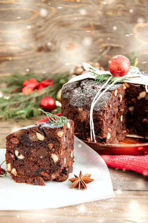 Slice and Whole Chocolate Christmas Pudding served on parchment paper with Xmas decorations. Wooden background. Toned.