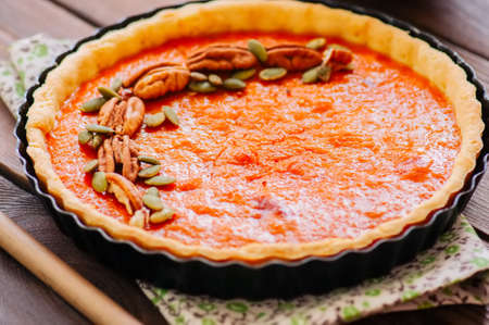 Pumpkin pie - traditional american dessert garnished with pecans and seeds on a wooden background Foto de archivo
