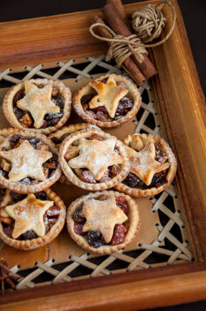 Mince pies in a wooden frame board. Traditional Christmas baking.