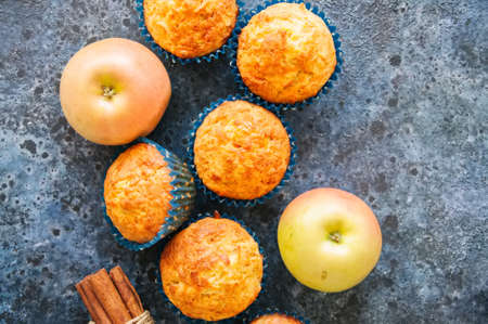 Homemade apple cheese muffins on a wire rack. Blue stone background. Seasonal baking. Archivio Fotografico