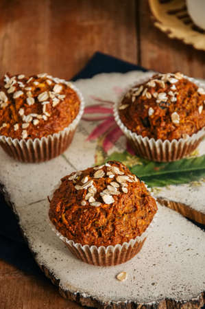 Healthy carrot cake muffins on a wooden board.