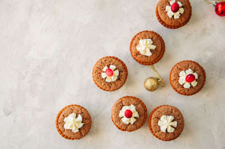 Brownie mins pies with cranberries on a white stone background