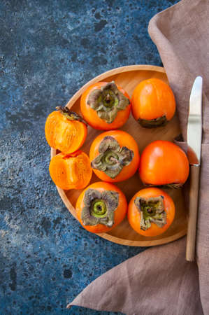 Fresh ripe persimmons on a wooden plate on a blue stone background