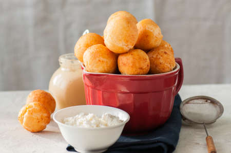 Small cottage cheese doughnuts (castgnole) served on a red  bowl.