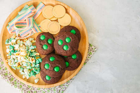 Sweet treats for St. Patricks day - Chocolate cookies, green popcorn, rainbow chewing marmalade and golden chocolate coins