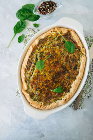 Quiche with spinach and cheese - savoty tart from flaky dough on a white stone backround with copy space.