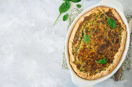 Quiche with spinach and cheese - savory tart from flaky dough on a white stone backround with copy space. Stock Photo