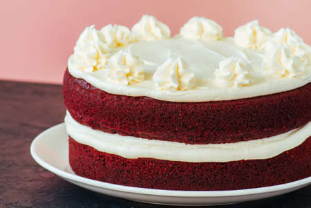 Red velvet cake with cream cheese frosting on a white plate