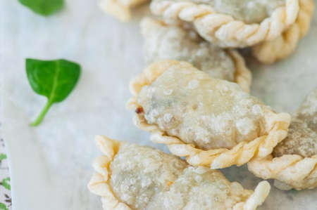 Fried savory pasties - hand pies with spinach on a white background. Top view and copy space. Stock Photo