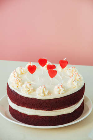 Red velvet cake with cream cheese frosting and heart shaped red candles on a white plate