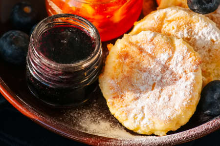 Top view of homemade cottage cheese pancakes- syrniki in a plate, jam on a wooden backdrop. Close up. Stock Photo