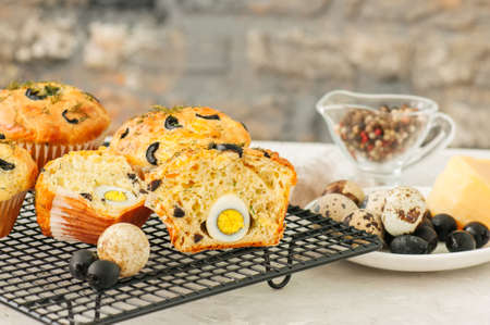 Savory muffins with olives, quail eggs and herbs on a wire rack on a white stone backdrop. Rustic style.
