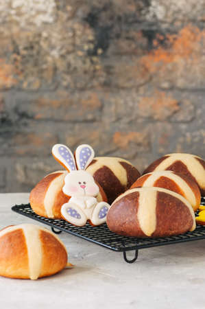 Chocolate and classic hot cross buns on a white stone background. Copy space.