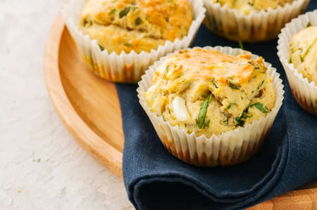 Savory muffins with feta cheese and spinach on a wooden plate on a white stone backdrop.  Stock Photo