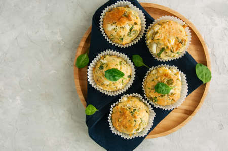 Savory muffins with feta cheese and spinach on a wooden plate on a white stone backdrop. Top view and copy space.