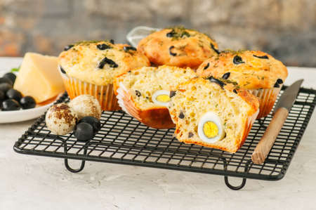 Savory muffins with olives and herbs on a wire rack on a white stone backdrop.  Stock Photo
