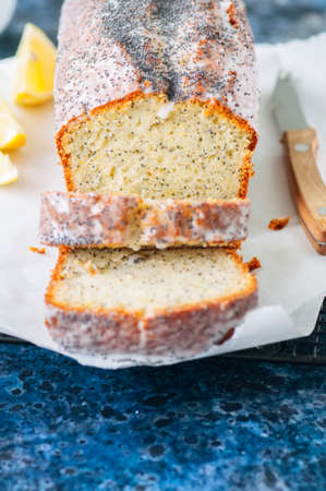 Slices of homemade lemon poppy seed pound cake on a wire rack. Blue stone background. Close up.