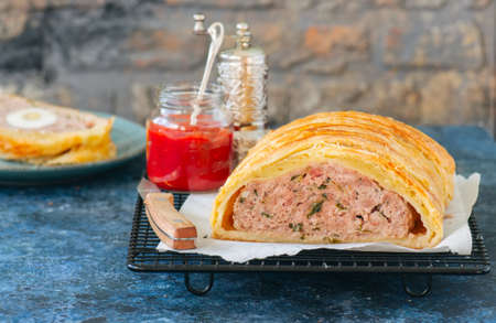 Turkey meatloaf in a puff pastry served on a wire rack. Blue stone backdrop.