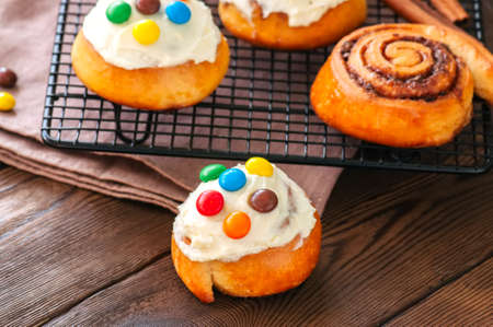 Classic cinnamon rolls - cinnabons with cream cheese frosting with smarties. Wooden background.