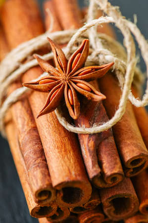 Close up of tied cinnamon sticks and anise star, Black slate background.