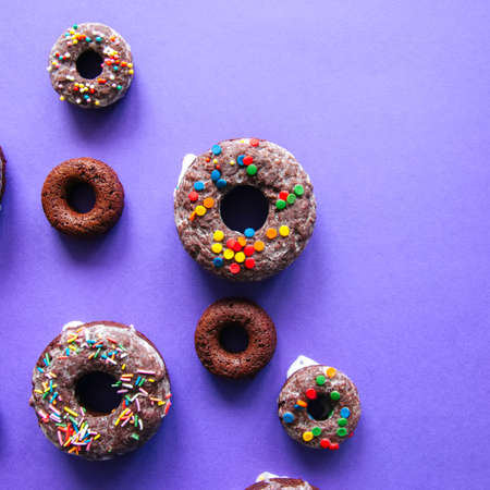 Baked chocolate doughnuts with glaze and confectionary topping on a violet background. Top view. Square image.