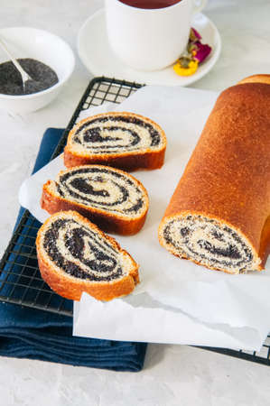 Traditional polish festive pastry - Makowiec- Poppy seed roll served on a wire rack. White stone background.