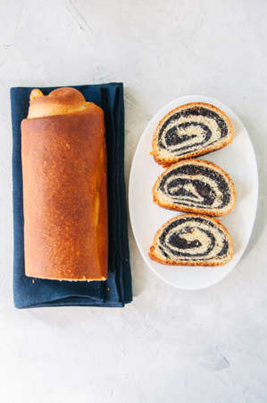 Traditional polish festive pastry - Makowiec- Poppy seed roll served on a wooden plate. White stone background.